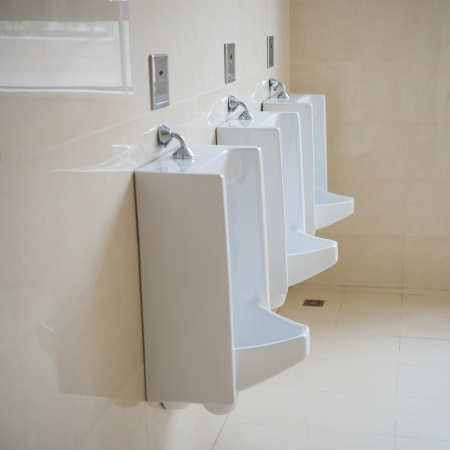 Row of three urinals in male toilet.  photo