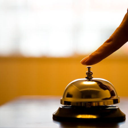 reception counter: Hand ringing in service bell on wooden table.