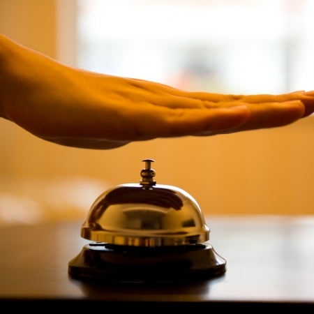hospitality industry: Hand ringing in service bell on wooden table.