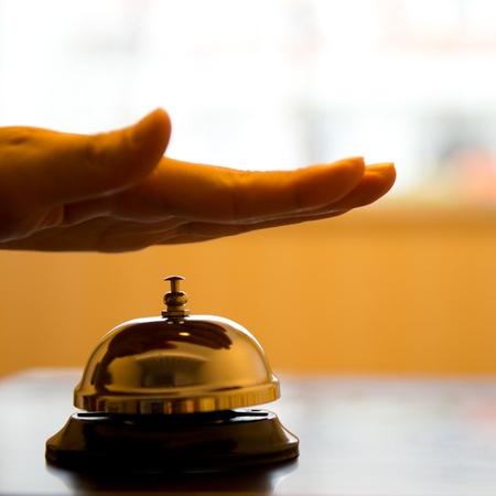 Hand piep in dienst bel op houten tafel. Stockfoto