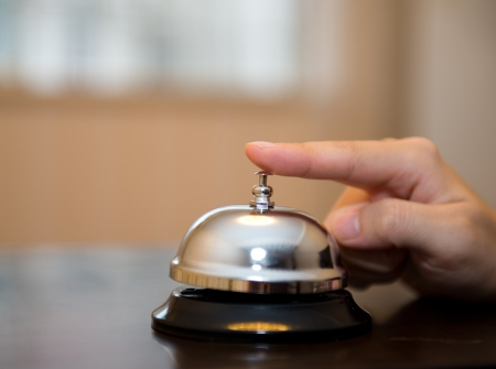 Hand ringing in service bell on wooden table. Stock Photo - 17828108