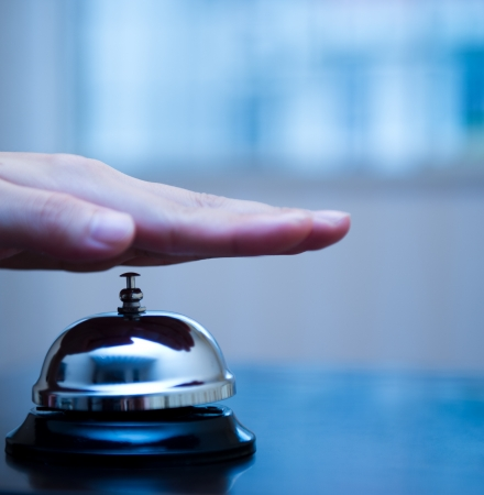 concierge: Hand ringing in service bell on wooden table.