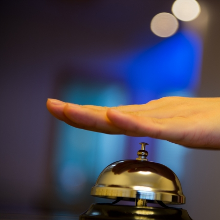 Hand ringing in service bell on wooden table. photo
