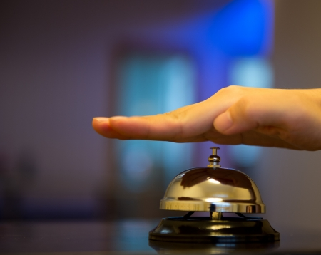 Hand ringing in service bell on wooden table. Stock Photo - 17828090