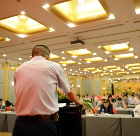 Business man is making a speech in front of a big audience at a conference hall. photo