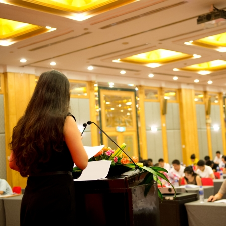 women talking: Business woman is making a speech in front of a big audience at a conference hall.