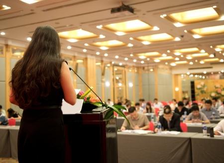 hablar en publico: Mujer de negocios que está haciendo un discurso frente a una gran audiencia en una sala de conferencias. Foto de archivo
