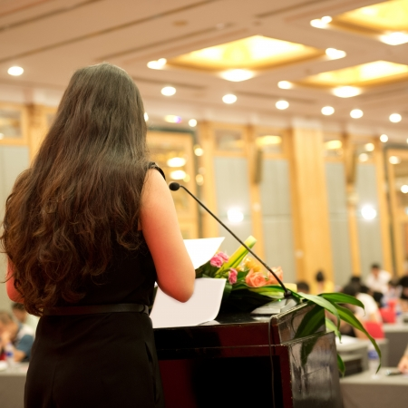 Business woman is making a speech in front of a big audience at a conference hall. photo