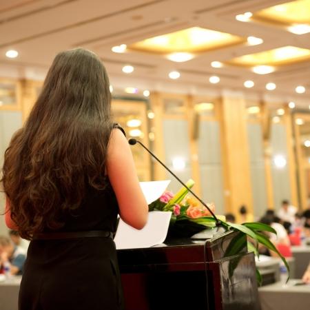 hablar en publico: Mujer de negocios que est� haciendo un discurso frente a una gran audiencia en una sala de conferencias. Foto de archivo