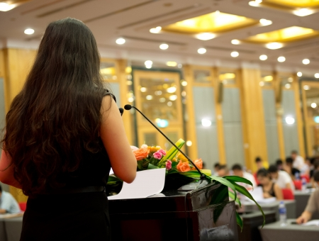 public speaking: Business woman is making a speech in front of a big audience at a conference hall.