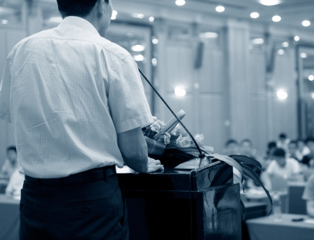 public speaking: Business man is making a speech in front of a big audience at a conference hall. Stock Photo