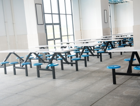 comedor escolar: Limpie cafetería de la escuela con muchos asientos vacíos y tablas.