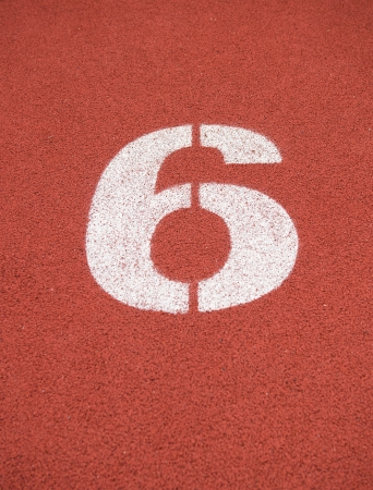 sixth: Number six on the start of a running track.