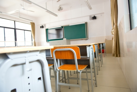 Empty classroom with chairs, desks and chalkboard. photo