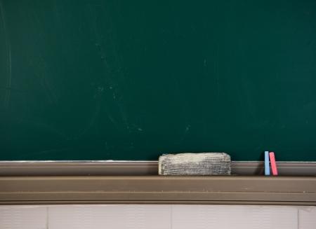 Blank blackboard with chalk and eraser.