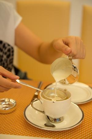 tomando refresco: Mujer vertiendo leche en la taza llena de té.
