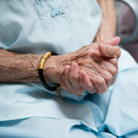 old age care: wrinkled hands  of old woman. Stock Photo
