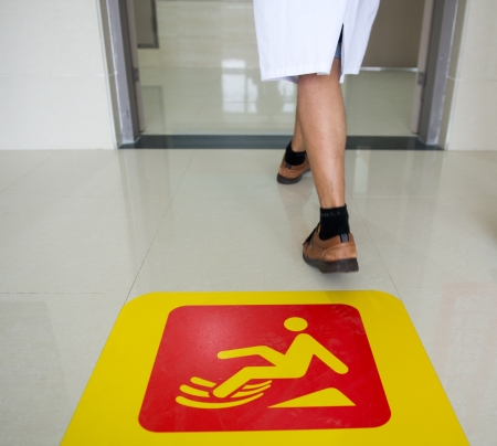 slippery: Yellow sign on floor that alerts for wet floor.  Stock Photo