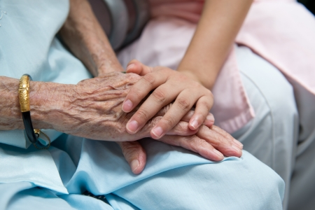 Mano chica joven toca y mantiene las manos arrugadas de una anciana. Foto de archivo