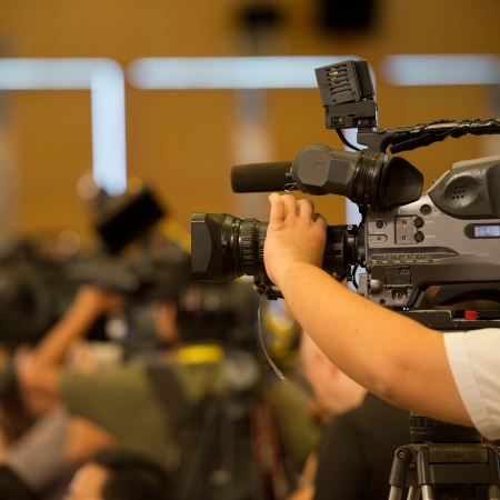 convention: journalist in a row with video camera for tv reportage.
