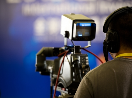 filming: journalist in a row with video camera for tv reportage.