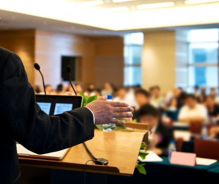 hablar en publico: El hombre de negocios está dando un discurso en frente de una gran audiencia en una sala de conferencias.