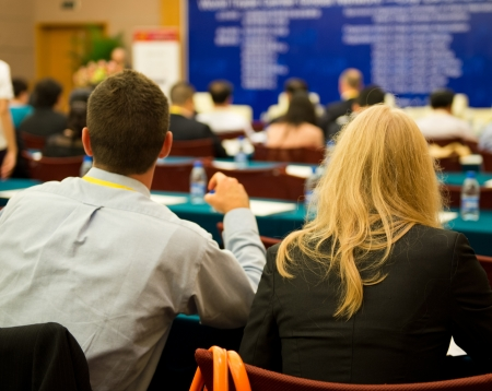 back training: Rear view of business people listening attentively at conference.