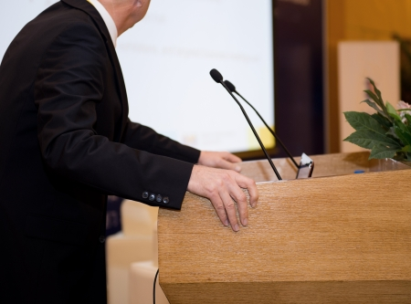 debates: Business man is making a speech in front of a big audience at a conference hall.