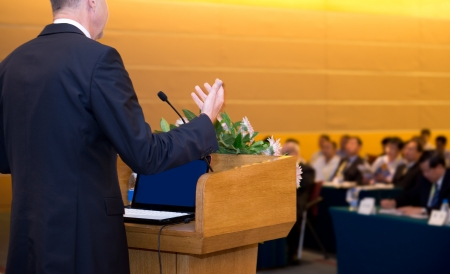 convention hall: Business man is making a speech in front of a big audience at a conference hall.