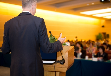 public speaking: Business man is making a speech in front of a big audience at a conference hall.