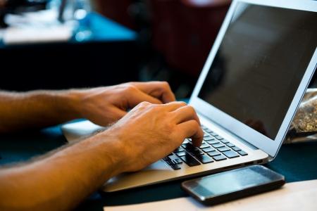 netbook: Human hands typing on laptop keyboard.