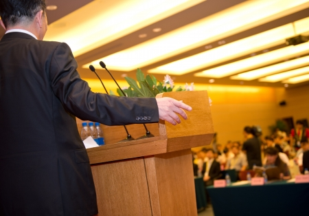 rostrum: Business man is making a speech in front of a big audience at a conference hall.