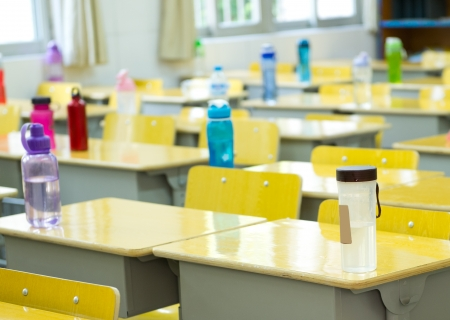 desk and chairs in classroom. Stock Photo