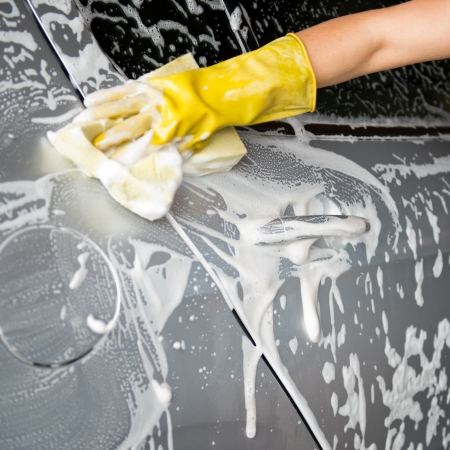 washing car: hand hold yellow sponge over the car for washing. Stock Photo