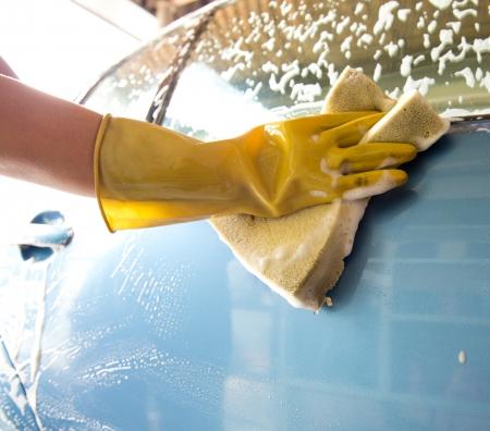lavarse las manos: asimiento de la mano una esponja amarilla sobre el coche para el lavado.