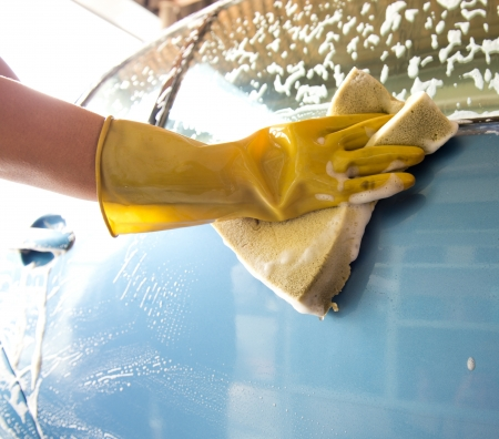 hand hold yellow sponge over the car for washing. Stock Photo