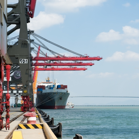 Industrial container cargo freight ship with working crane bridge.  photo
