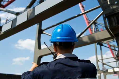 walkie: engineer in hard-hat overlooking large commercial container port. Stock Photo