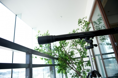 A telescope setting near the window. Stock Photo - 19279414