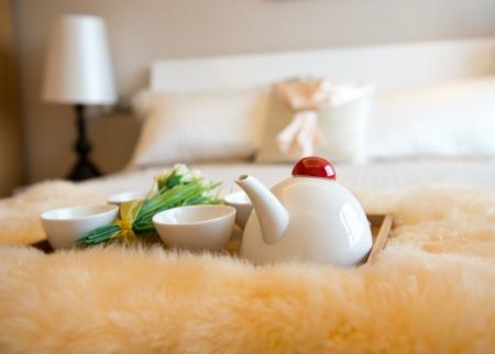 desayuno romantico: interior del dormitorio de lujo con la bebida en la cama. Foto de archivo
