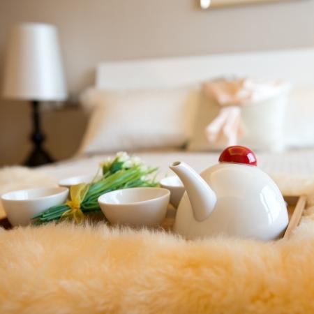 romantic room: luxury bedroom interior with beverage on bed.