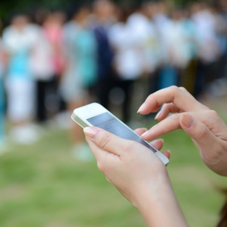 input device: Close up of woman using mobile smart phone in the park.