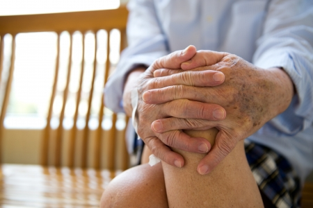 intersect: Old man sitting with his hands on knee. Stock Photo