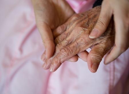 pacientes: La mano de la chica joven toca y tiene las manos arrugadas de una anciana.