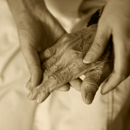 elderly care: Young girls hand touches and holds an old womans wrinkled hands.