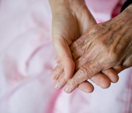 personas ayudando: La mano de la chica joven toca y tiene las manos arrugadas de una anciana.