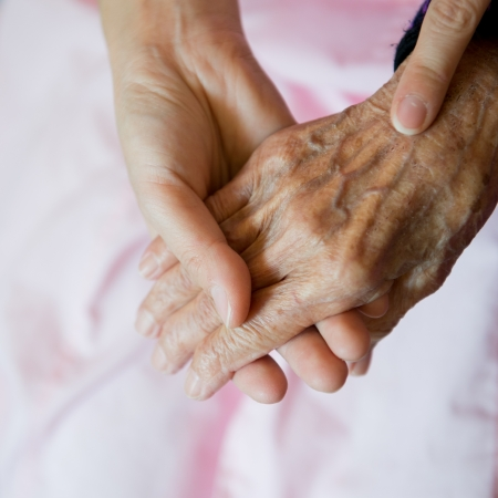 Young girls hand touches and holds an old womans wrinkled hands. photo