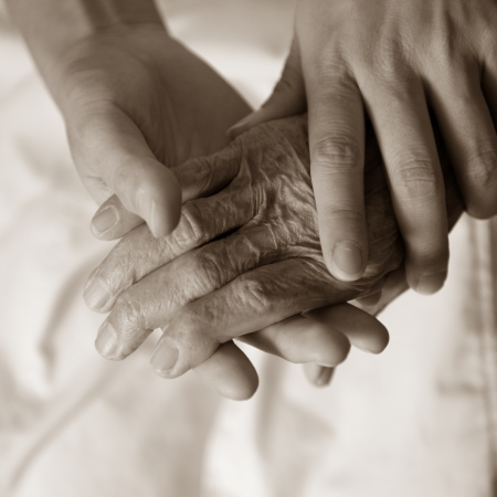 old age care: Young girls hand touches and holds an old womans wrinkled hands.