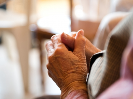 confess: Old womans hands clasped praying.