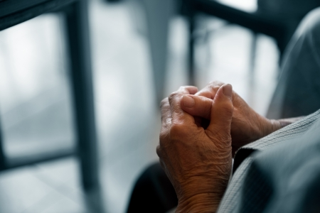 to implore: Old womans hands clasped praying.